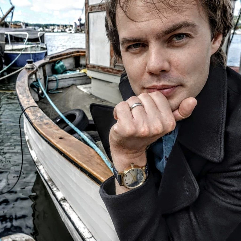 Image of Holme Finnilä, founder of Levenaig Watches, sitting on a boat, waiting for someone to contact him.; wears a handmade watch in order to know what time it is.